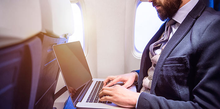 8 ways to avoid being hacked when traveling business man on plan typing on laptop