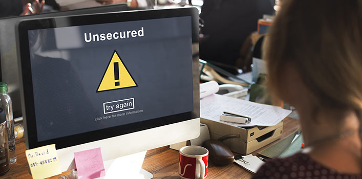 woman sitting at desk looking at computer screen with unsecured warning sign
